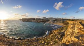 Ghajn Tuffieha, Malta - Panoramic skyline view of Golden Bay, Ma. Lta`s most beautiful sandy beach at sunset with blue sky and clouds Royalty Free Stock Photography