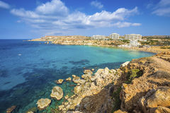 Ghajn Tuffieha, Malta - Panoramic skyline view of Golden Bay. Malta`s most beautiful sandy beach on a nice summer day with blue sky and clouds Stock Photos