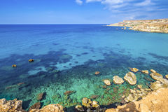 Ghajn Tuffieha, Malta - Panoramic skyline view of Golden Bay. Malta`s most beautiful sandy beach on a nice summer day with blue sky and clouds Royalty Free Stock Photo