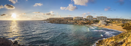 Ghajn Tuffieha, Malta - Panoramic skyline view of Golden Bay. Malta`s most beautiful sandy beach at sunset with blue sky and clouds Royalty Free Stock Image