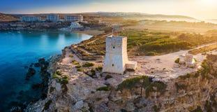 Ghajn Tuffieha, Malta - Piękny wschód słońca przy Ghajn Tuffieha zegarka wierza z Złotą zatoki plażą obrazy stock