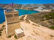 Ghajn Tuffieha, Malta - Piękny Ghajn Tuffieha zegarka wierza i Złota zatoka wyrzucać na brzeg na jaskrawym letnim dniu obraz royalty free