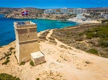 Ghajn Tuffieha, Malta - Piękny Ghajn Tuffieha zegarka wierza i Złota zatoka wyrzucać na brzeg od above fotografia stock