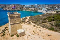 Ghajn Tuffieha, Malta - Piękny Ghajn Tuffieha zegarka wierza i Złota zatoka wyrzucać na brzeg od above obraz royalty free