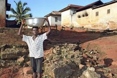 Ghanaian Boy carries scale with water on his head Royalty Free Stock Photos