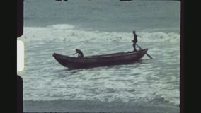 Fishing Boat Arriving At Shore. GHANA, BUSUA, APRIL 1976. Wide Shot With Zoom In, Of A Small Fishing Boat With Two Men On Board Arriving At Shore. One Man stock video footage
