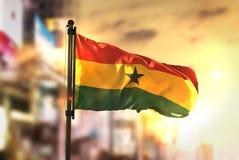 Ghana flagga mot suddig bakgrund för stad på soluppgångpanelljuset arkivfoton