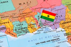 Ghana map and a flag pin. Ghana paper flag pin on a world map. Officially the Republic of Ghana, it is located along the Gulf of Guinea and Atlantic Ocean, in stock image