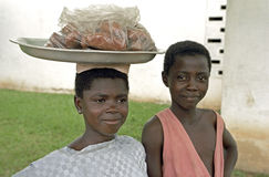 Ghanaian Brother and sister sell food in Kumasi. Group Portrait of street sellers. This girl is selling croquettes in the city Kumasi [capital of the region Stock Image
