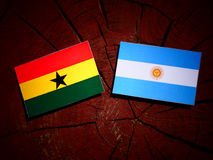 Ghanaian flag with Argentinian flag on a tree stump  Royalty Free Stock Photo
