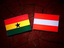 Ghanaian flag with Austrian flag on a tree stump  Stock Image