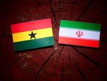 Ghanaian flag with Iranian flag on a tree stump isolated Royalty Free Stock Photos