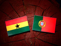 Ghanaian flag with Portuguese flag on a tree stump isolated. Ghanaian flag with Portuguese flag on a tree stump vector illustration