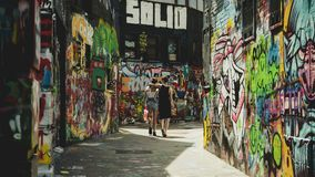 Couple walking down Graffiti Street stock photo