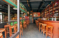 Empty bar with wooden tables, bottles, drinks and colorful decoration. GHENT, BELGIUM - MAR 30, 2018: Empty bar with wooden tables, bottles, drinks and colorful stock images