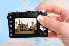 Ghent Belgium. Woman's tourist hand holds camera taking a picture of Ghent, Belgium in sepia tone with blurred map of Europe in the background Royalty Free Stock Photos