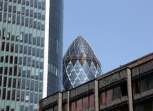The Gherkin enframed by surrounding buildings Royalty Free Stock Image