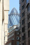 The Gherkin enframed by surrounding buildings Stock Images