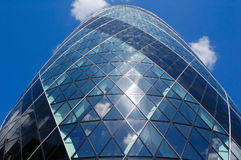 The Gherkin skyscraper in London. Vertical view of the Gherkin skyscraper with a blue sky background Royalty Free Stock Photo