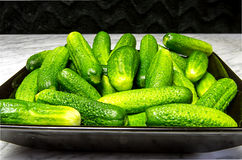 Gherkins on a black plate. On a marble table Stock Photo