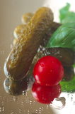 Gherkins pickled cherry tomatoes and fresh basil leaves Royalty Free Stock Photography