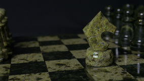Ghess white horse defeats black pawn. Selective focus. Chess, Horse and pawn. Details of chess piece on black background. 4K Royalty Free Stock Photos