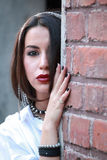 A ghetto styled girl in front of brick wall Royalty Free Stock Photography