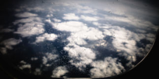 Ghiacci i fiori sulla finestra dell'aeroplano, con le montagne e le nuvole nel fondo Immagini Stock