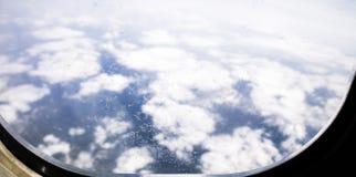 Ghiacci i fiori sulla finestra dell'aeroplano, con le montagne e le nuvole nel fondo Fotografia Stock