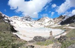 Ghiacci il lago contro lo sfondo delle pietre innevate delle montagne nella priorità alta Fotografia Stock Libera da Diritti