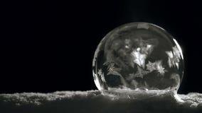 Ghiacci la sfera di cristallo che si congela sulla neve su fondo nero stock footage