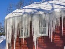 Ghiacci le dighe e la neve sul tetto e sulle grondaie Immagini Stock Libere da Diritti