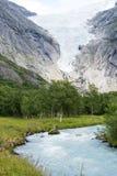 Ghiacciaio di Briksdalsbreen ad estate con il fiume della montagna da ghiaccio fuso su priorità alta Immagine Stock