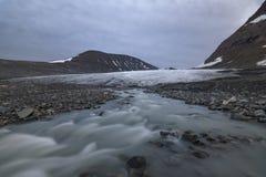 Ghiacciaio sereno con il fiume che sorge sotto, parco nazionale di Sarek, Svezia Immagini Stock