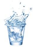 Ghiaccio che spruzza in tazza di acqua Fotografia Stock