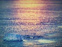 Ghiaccio freddo brillante, ghiaccioli luminosi sulla riva congelata del lago Raggi caldi del sole del tramonto riflessione Fotografie Stock Libere da Diritti