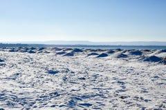 Ghiaccio, neve e dune di sabbia congelati sulla spiaggia con le colline nella distanza Fotografia Stock