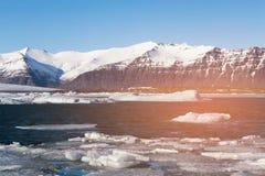 Ghiaccio sulla laguna blu di Jakulsarlon con il fondo della roccia del vulcano Fotografia Stock