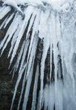 Ghiaccioli che appendono accanto ad una cascata congelata Immagine Stock Libera da Diritti