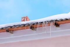 Ghiaccioli che appendono sul tetto di una costruzione rosa Tempo caldo e soleggiato piacevole fotografia stock libera da diritti