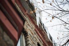 Ghiaccioli che pendono dal tetto della costruzione Fotografie Stock Libere da Diritti