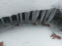 Ghiaccioli che pendono giù dal bordo della neve sopra la corrente fotografia stock