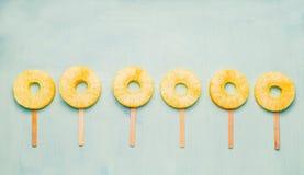 Ghiaccioli della fetta dell'ananas sul fondo leggero del turchese, vista superiore Alimento sano Immagini Stock Libere da Diritti