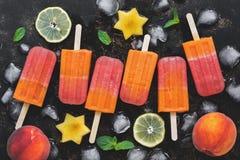 Ghiaccioli della pesca con frutta, il limone ed i cubetti di ghiaccio su un fondo scuro Vista superiore, disposizione piana fotografia stock