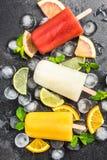 Ghiaccioli sani casalinghi del succo naturale sopra i cubetti di ghiaccio immagine stock