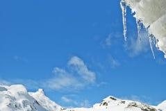 Ghiaccioli su un tetto con neve. Fotografie Stock Libere da Diritti