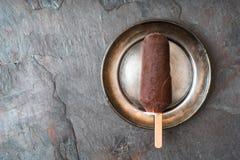 Ghiacciolo coperto di cioccolato nel di piastra metallica sulla vista superiore del fondo di pietra Immagine Stock Libera da Diritti