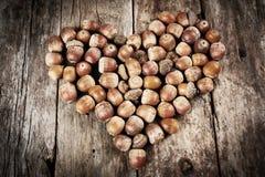 Ghiande che formano un cuore su un fondo di legno Immagini Stock