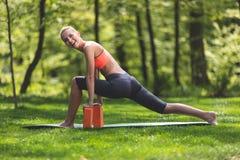Ghignare la donna è prepararsi con i blocchetti di yoga all'aperto Fotografia Stock Libera da Diritti