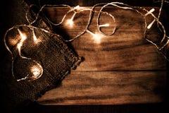 Ghirlanda d'ardore delle luci di Natale su un vecchio parque di legno antico Immagini Stock Libere da Diritti